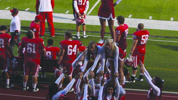 Denison cheerleaders form a pyramid during a football game in the fall. The cheerleading squad is actively recruiting new members for the 2014-15 school year.